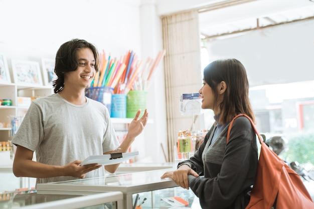 Jong meisje dat een kantoorboekhandel bezoekt, praat met de mannelijke kassier