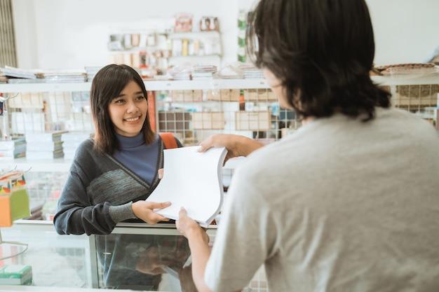 Jong meisje dat een kantoorboekhandel bezoekt, praat met een mannelijke kassier die papier koopt