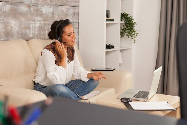 Jong meisje dat een koptelefoon draagt tijdens online sollicitatiebriefing vanuit huis.