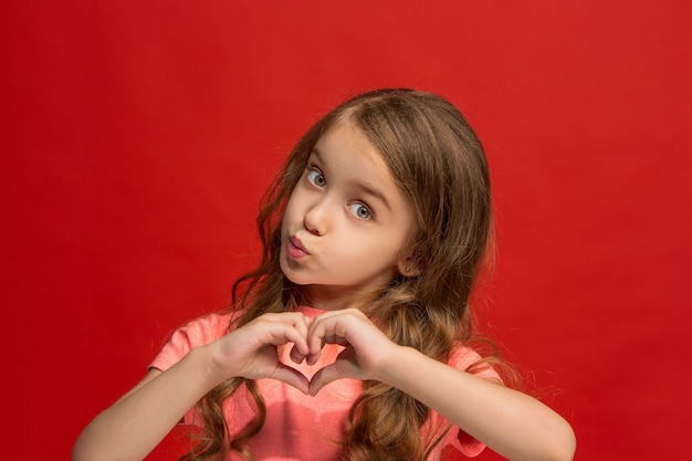 Jong meisje dat een kus verzendt en hart met handen ondertekent