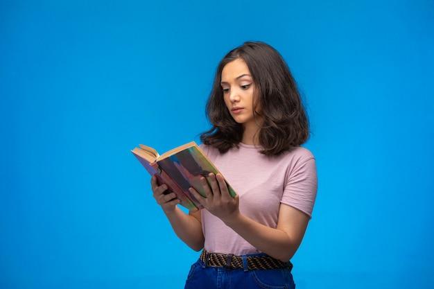 Jong meisje dat een oud boek leest en denkt.