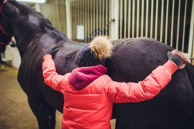 Jong meisje dat een paard koestert