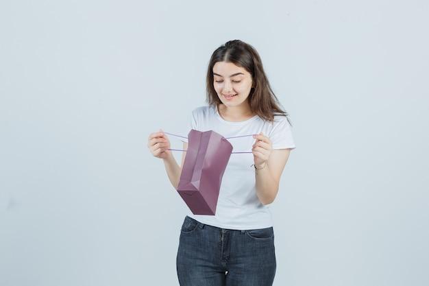 Jong meisje dat een papieren zak in t-shirt, jeans onderzoekt en gelukkig kijkt. vooraanzicht.