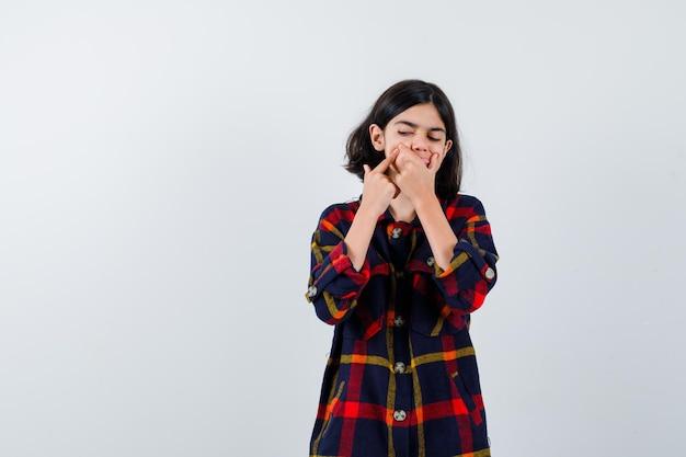 Jong meisje dat een puistje in een geruit overhemd knalt en er gefocust uitziet, vooraanzicht.