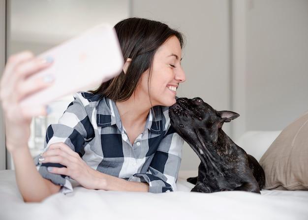Jong meisje dat een selfie met haar hondje neemt