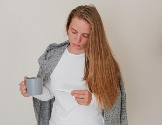 Jong meisje dat een thermometer en een grijze mok met hete drank houdt
