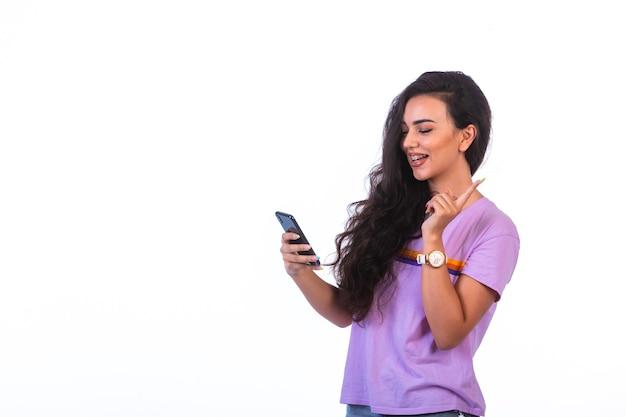 Jong meisje dat een videogesprek met een zwarte smartphone heeft.