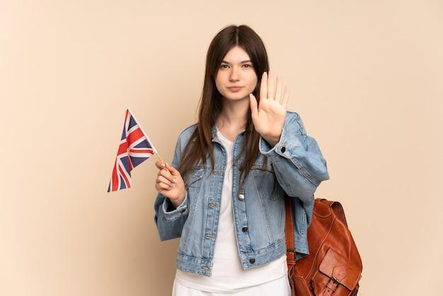 Jong meisje dat een vlag van het verenigd koninkrijk houdt die op beige wordt geïsoleerd die stopgebaar maakt