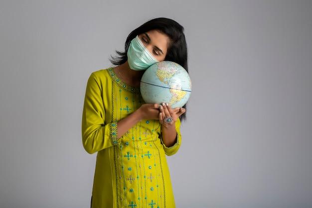 Jong meisje dat en wereldbol met een medisch gezichtsmasker op grijze achtergrond houdt stelt.
