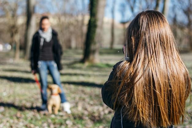 Jong meisje dat foto van haar moeder in het park neemt