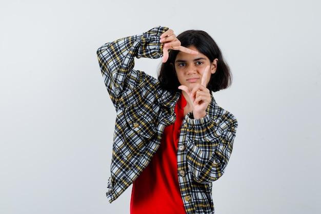 Jong meisje dat framegebaar in geruit overhemd en rood t-shirt toont en er serieus uitziet. vooraanzicht.