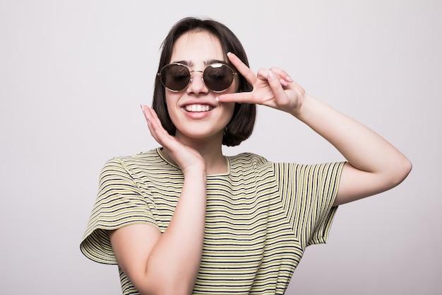 Jong meisje dat geïsoleerd zonnebril draagt. close-up portret