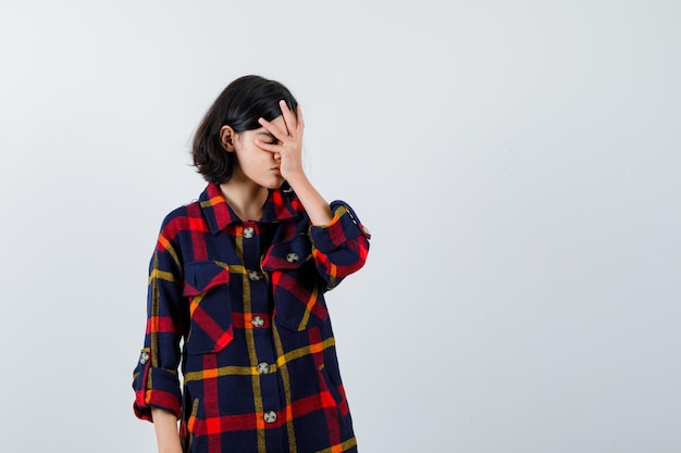 Jong meisje dat gezicht bedekt met hand in geruit overhemd en geïrriteerd kijkt, vooraanzicht.