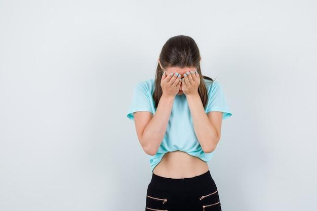 Jong meisje dat gezicht bedekt met handpalmen in turquoise t-shirt, broek en boos kijkt, vooraanzicht.