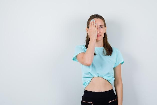 Jong meisje dat gezicht bedekt met palm in turquoise t-shirt, broek en nieuwsgierig kijkt, vooraanzicht.
