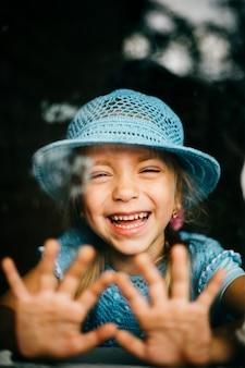 Jong meisje dat gezichten maakt en door venster met palmen lacht die erop liggen. expressieve kindemoties. dramatisch gelukkig kindgezicht.