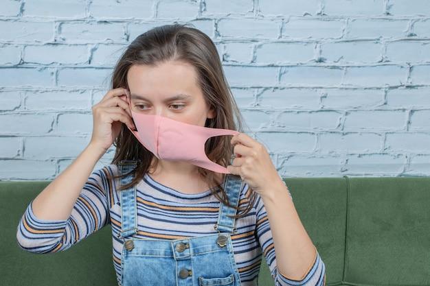 Jong meisje dat gezichtsmasker draagt om covid-virus te voorkomen