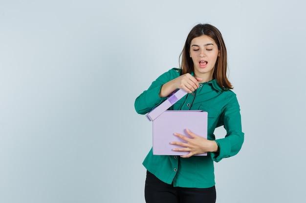 Jong meisje dat giftdoos in groene blouse, zwarte broek probeert te openen en opgewekt kijkt. vooraanzicht.