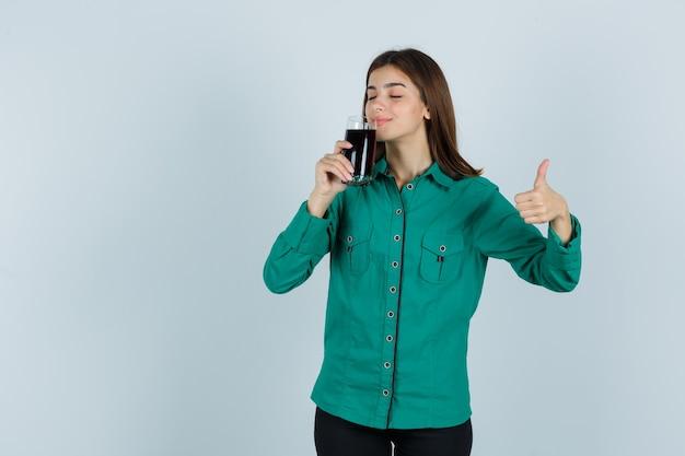 Jong meisje dat glas zwarte vloeistof probeert te drinken, duim in groene blouse, zwarte broek toont en gelukkig kijkt. vooraanzicht.