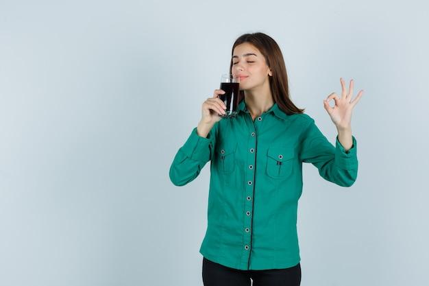 Jong meisje dat glas zwarte vloeistof probeert te drinken, ok teken in groene blouse, zwarte broek toont en gelukkig kijkt. vooraanzicht.