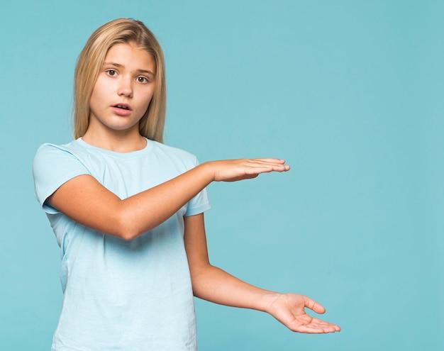 Jong meisje dat grootte met handen toont