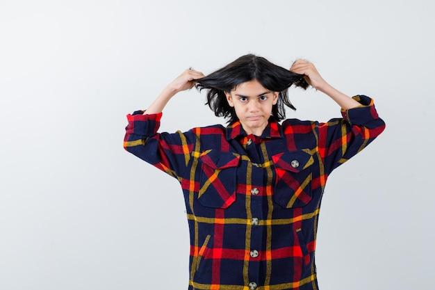 Jong meisje dat haar in een geruit overhemd stopt en er serieus uitziet. vooraanzicht.