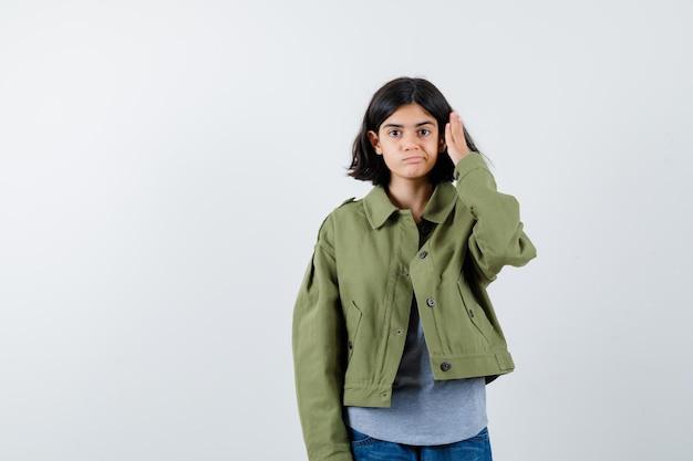 Jong meisje dat haar in een grijze trui, een kaki jasje, een spijkerbroek stopt en er serieus uitziet. vooraanzicht.