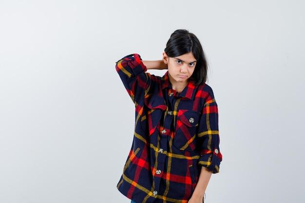 Jong meisje dat haar instopt terwijl ze in een geruit overhemd poseert en er charmant uitziet. vooraanzicht.