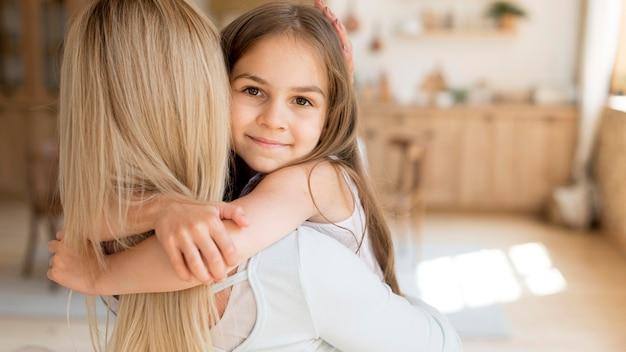 Jong meisje dat haar moeder thuis omhelst