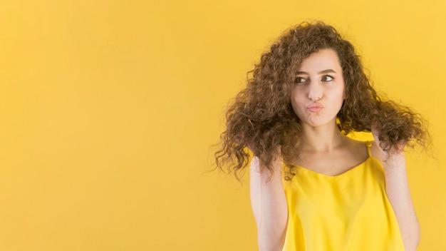 Jong meisje dat haar ruimte van het haarexemplaar schikt