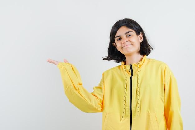 Jong meisje dat hand naar links uitrekt als iets denkbeeldigs vasthoudt in een geel bomberjack en er serieus uitziet
