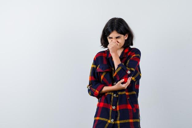 Jong meisje dat hand op mond legt, hand op elleboog houdt, probeert in geruit overhemd te niezen en er uitgeput uitziet. vooraanzicht.