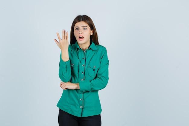 Jong meisje dat hand op verraste manier in groene blouse, zwarte broek opheft en geschokt, vooraanzicht kijkt.