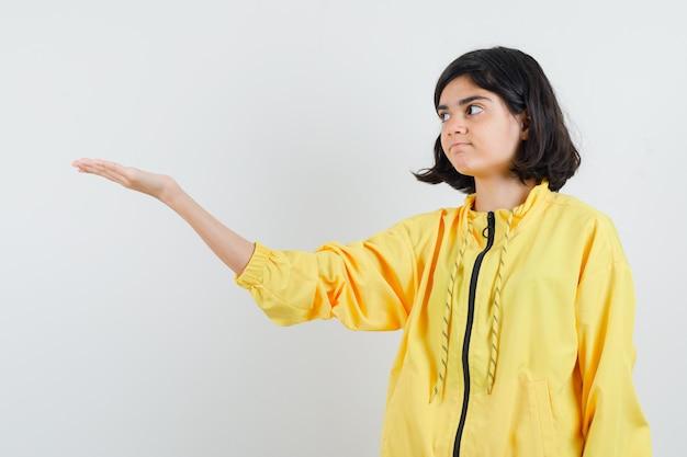 Jong meisje dat hand uitrekt als iets denkbeeldigs in geel bomberjack houdt en ernstig kijkt.