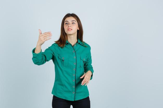 Jong meisje dat hand uitrekt als iets denkbeeldigs vasthoudt in groene blouse, zwarte broek en gefocust, vooraanzicht kijkt.