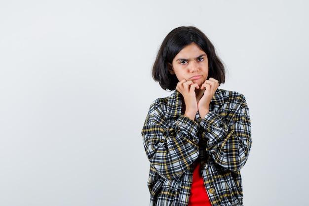 Jong meisje dat handen onder de kin legt, grimassen trekt in geruit overhemd en rood t-shirt en boos kijkt. vooraanzicht.