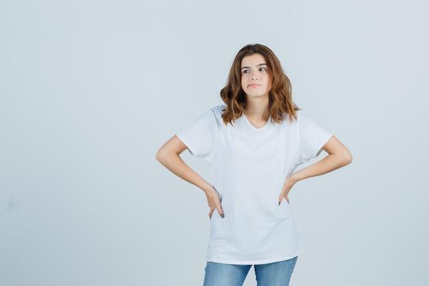Jong meisje dat handen op taille in wit t-shirt houdt en teleurgesteld kijkt. vooraanzicht.
