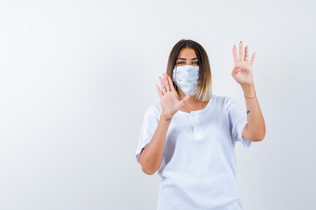 Jong meisje dat handpalmen opheft in overgave gebaar in wit t-shirt en masker en op zoek naar zelfverzekerd, vooraanzicht.
