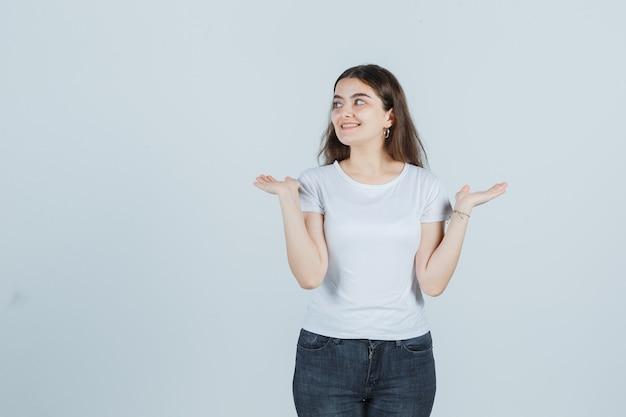Jong meisje dat handpalmen opzij in t-shirt, jeans uitspreidt en mooi, vooraanzicht kijkt.