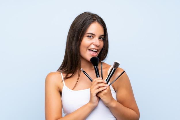 Jong meisje dat heel wat make-upborstel houdt