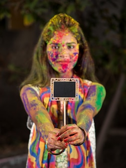 Jong meisje dat het kleine bord vasthoudt ter gelegenheid van het holi-festival met gezichten beschilderd met poederkleuren, met een kleurplons.