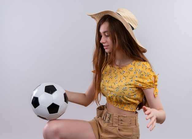 Jong meisje dat hoed draagt die met voetbal op geïsoleerde witte muur speelt