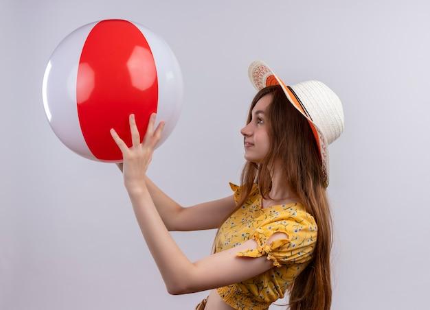 Jong meisje dat hoed draagt die strandbal opheft en bekijkt die zich in profielmening op geïsoleerde witte muur bevinden