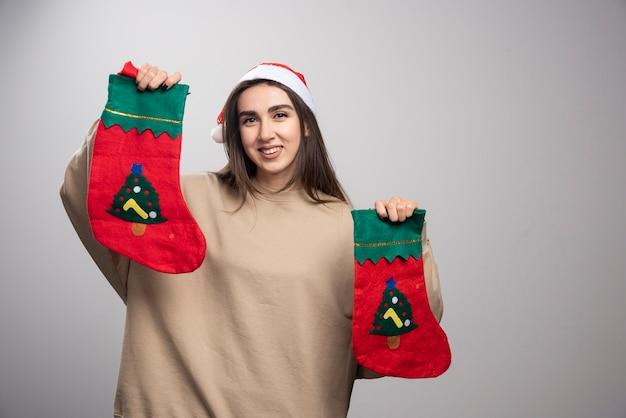 Jong meisje dat in de hoed van de kerstman twee kerstmissokken houdt.