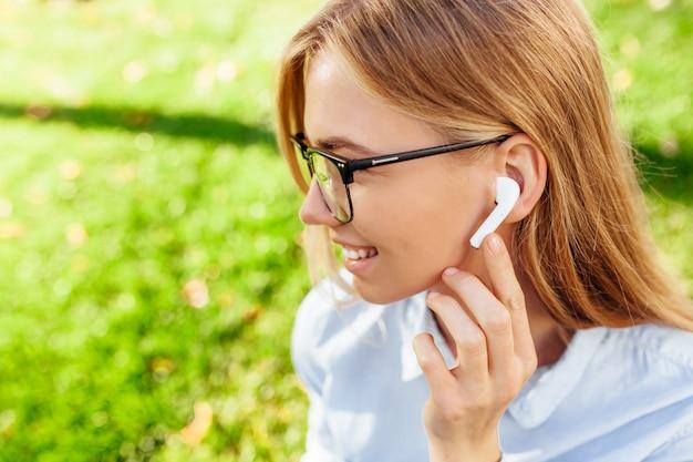 Jong meisje dat in glazen aan muziek door draadloze hoofdtelefoons in openlucht luistert