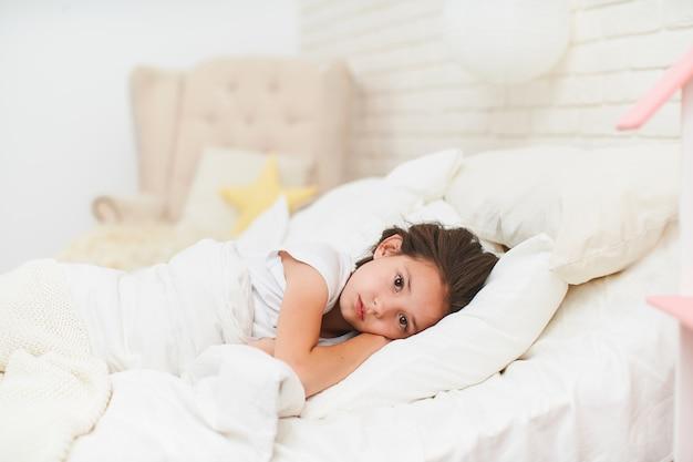 Jong meisje dat in haar bed ligt met haar handen onder haar hoofd