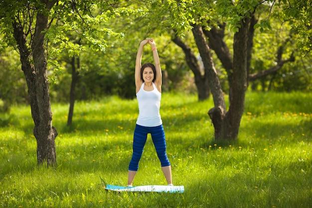 Jong meisje dat in openlucht uitwerkt. mooie vrouw doet pilates, yoga en fitness oefeningen op de natuur.