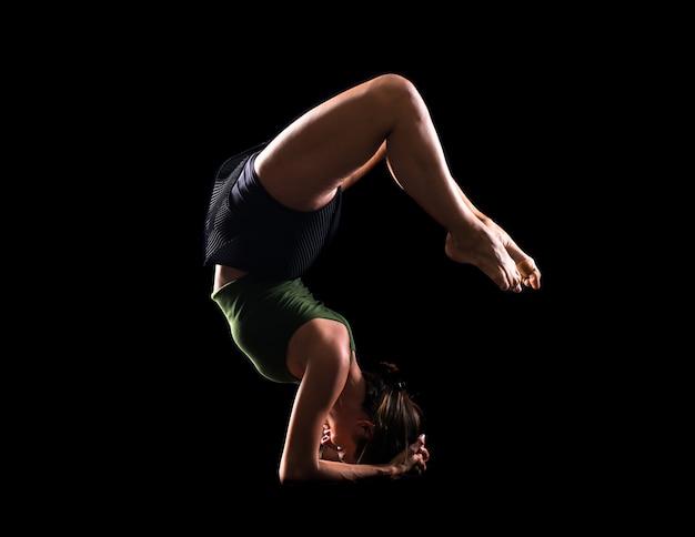 Jong meisje dat in studio op geïsoleerde achtergrond danst