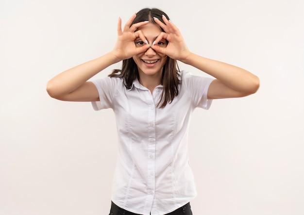Jong meisje dat in wit overhemd binoculair gebaar met vingers maakt die door vingers kijken die zich over witte muur bevinden
