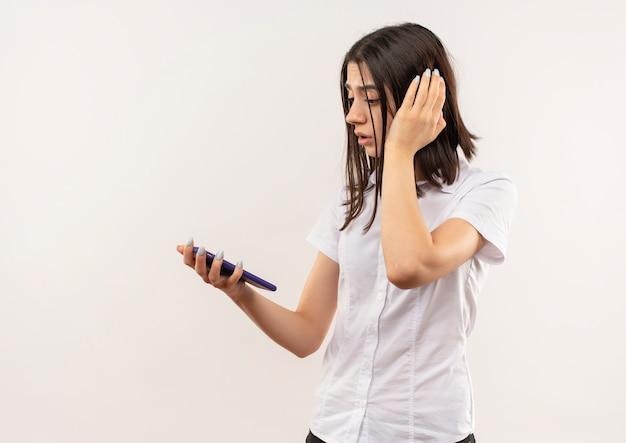 Jong meisje dat in wit overhemd het scherm van haar mobiele telefoon bekijkt verward status over witte muur
